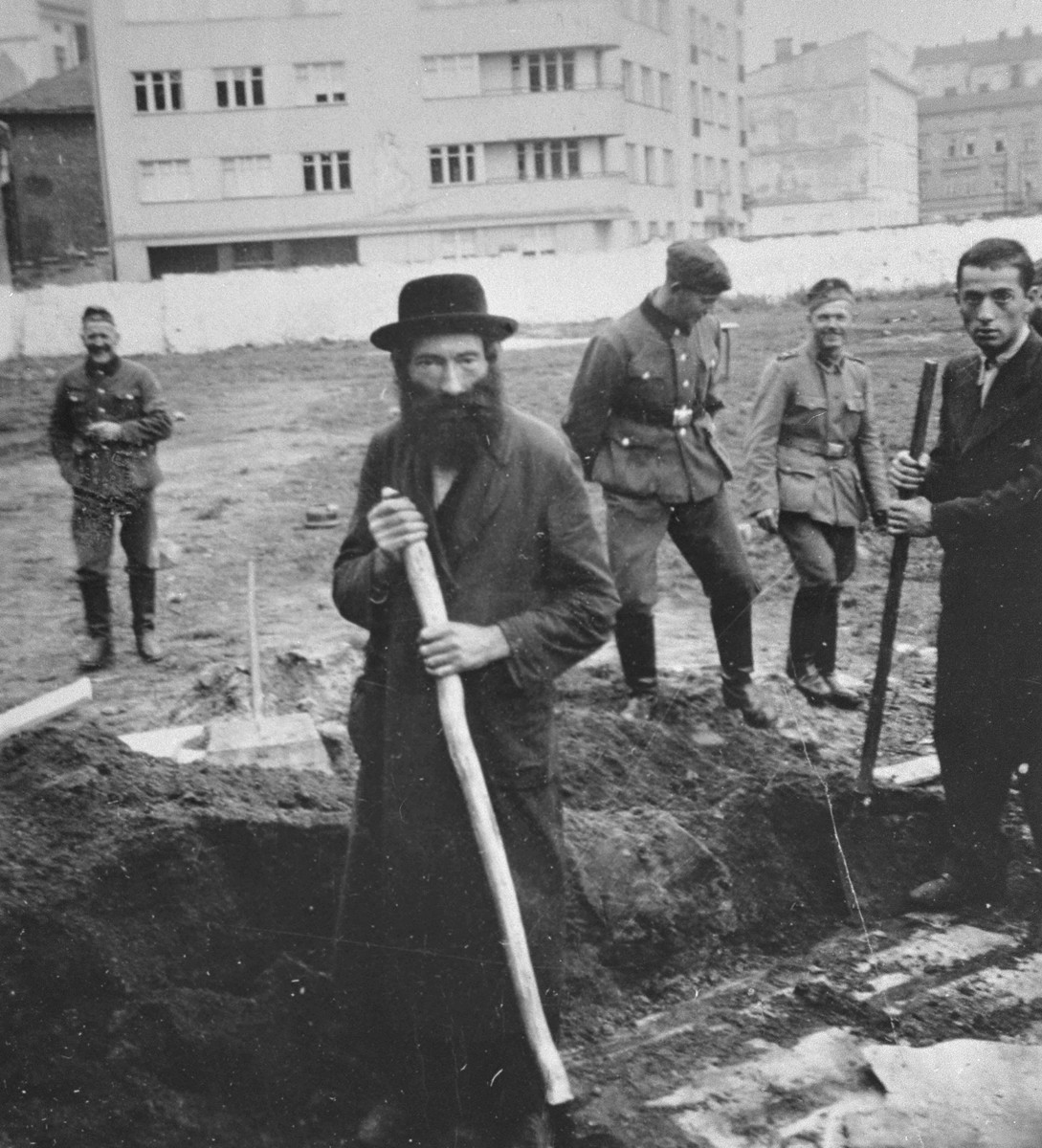 German soldiers amuse themselves while they force Jews to dig ditches in an empty lot in Krakow.