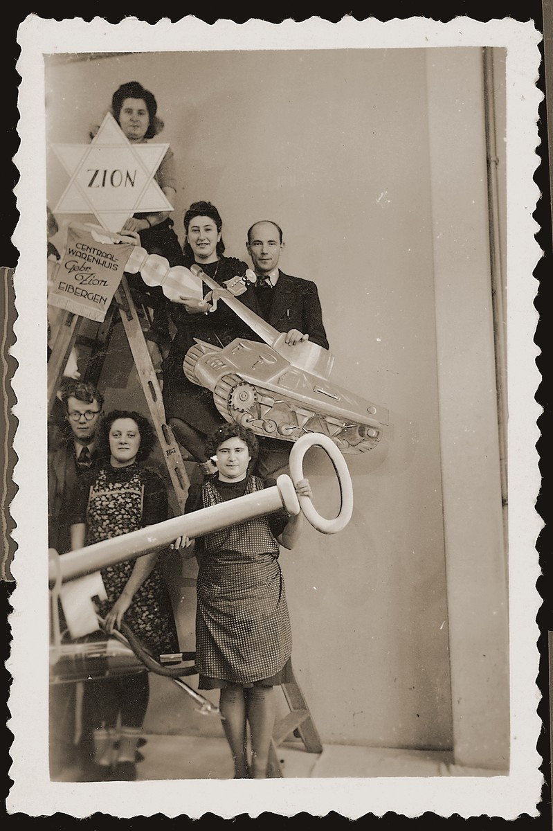 Employees pose with props for the festive reopening of the Zion clothing and fabric store in Eibergen.  Among those pictured are: Bep Meijer (to the right of the star), Mien Zion (top), and Frieda Zion (holding the key).