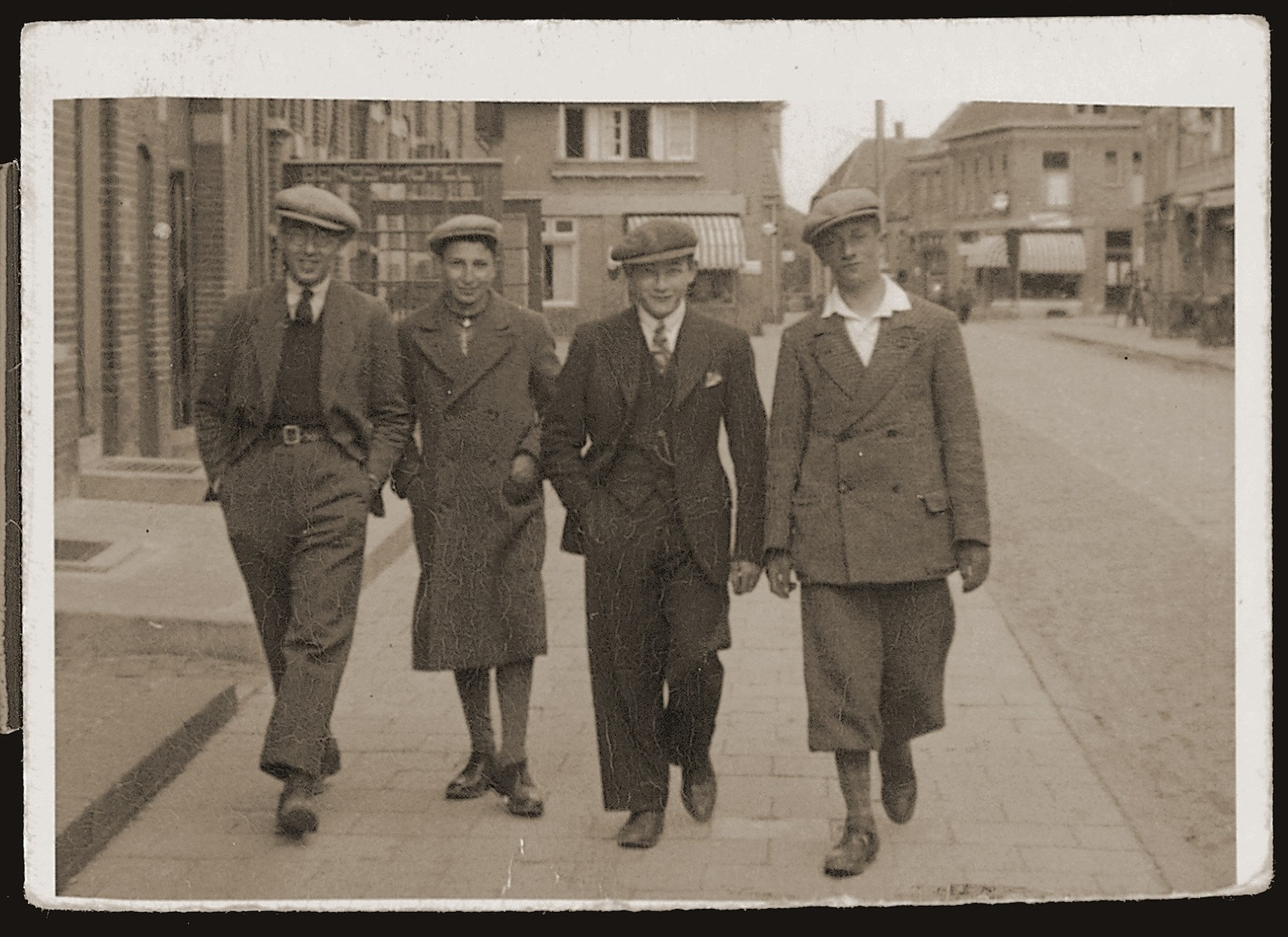 Four Jewish friends walk along a street in Boekelo.  Pictured from left to right are: Lou Slosser, Richard Meijer, Michel Meijer (cousin), and Meyer Godschalk.