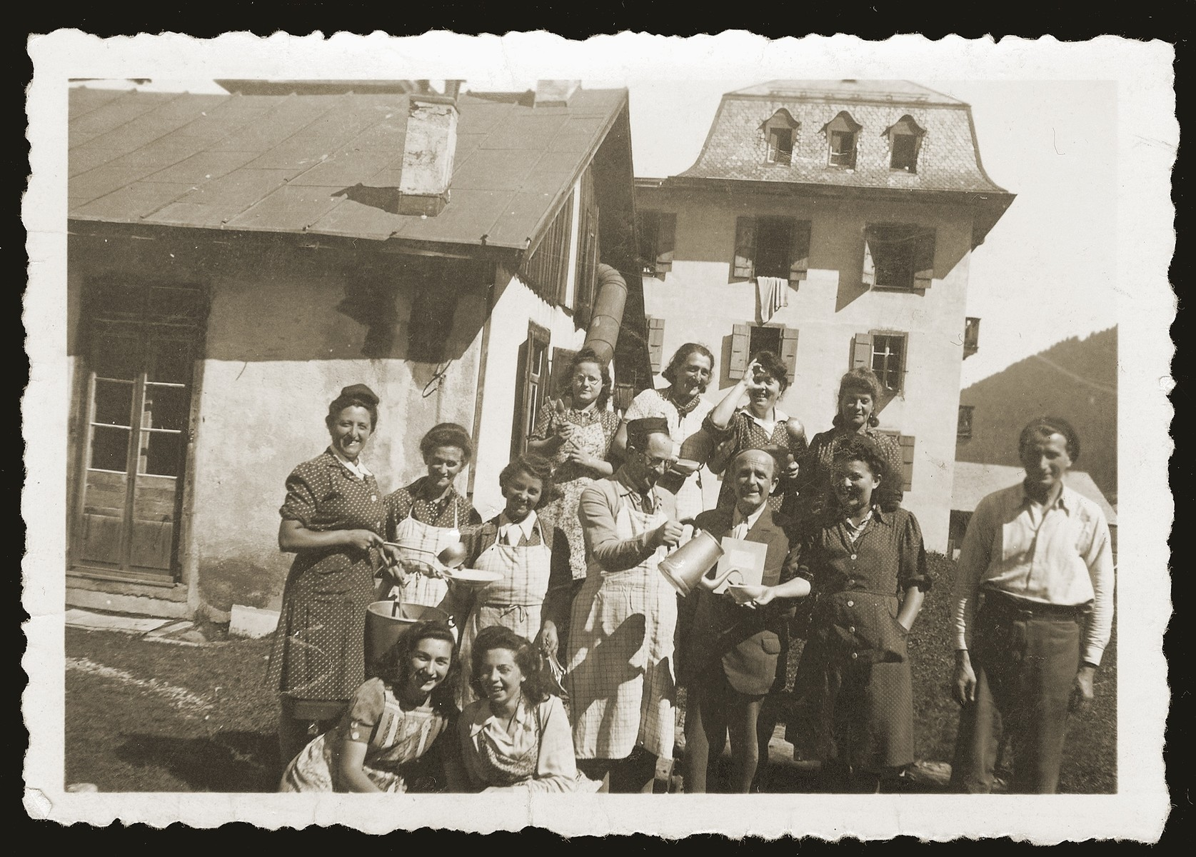 The kitchen staff of the Morgins family camp poses outside the main building.  Kasiel Aba Johles is seen in the center pouring a liquid.