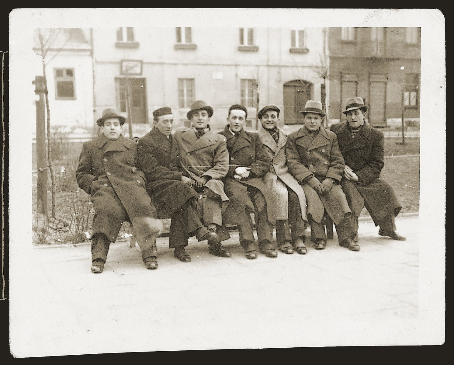A group of young men sits on an outdoor bench in Czeladz.  Lazar Heida is pictured second from the left.