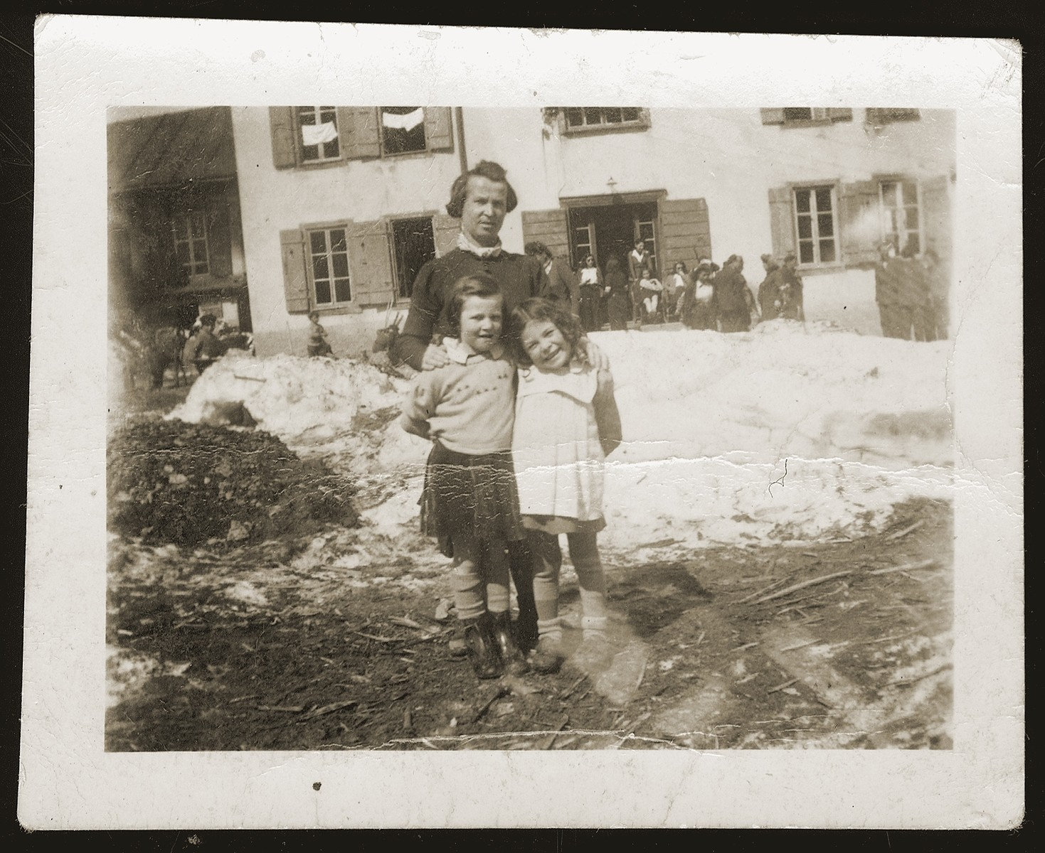 Frieda Johles poses with her mother, Malka Johles and a friend outside the main building of the Morgins family camp which housed the adults.
