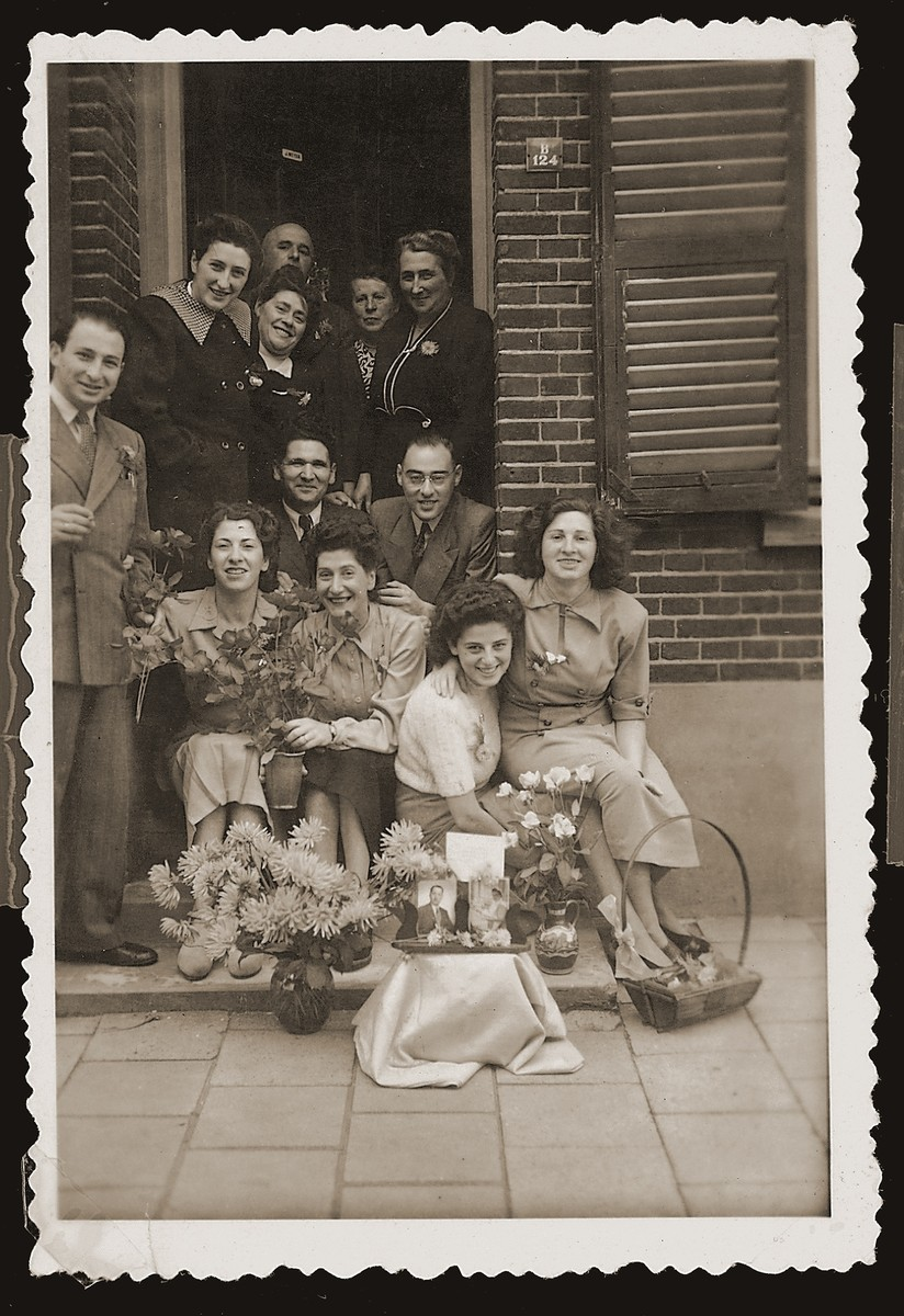 Bep Meijer (top left) with family and friends at the entrance to her family's home in Boekelo.  The photo was taken on the occasion of her sister's wedding in New York, which the family could not attend.  Pictures of the bride and groom appear in the foreground surrounded by flowers.  Bep's husband, Sallie Zion, is seated in the center below her.