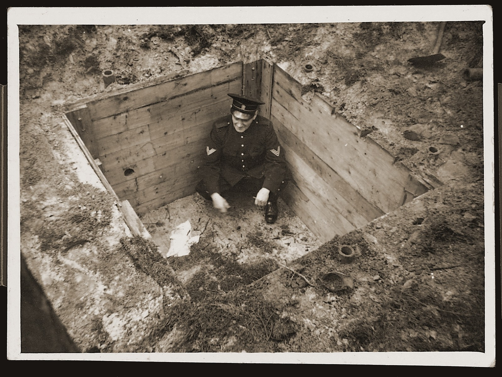 A Dutch policeman crouches inside a small bunker that served as a hiding place for Dutch Jews in the Eibergen region in 1942-1943.  The bunker was discovered by the Germans one day before this photograph was taken.  The bunker was, in actuality, a prefabricated hut that was ordered by two Jewish brothers, Abraham and Herman Maas from Eibergen.  It was delivered in sections to a site in the Hoones Forest outside Eibergen.  The Maas brothers got permission from the manager of the privately-owned forest to build a subterranean hiding place for themselves.  Two sympathetic non-Jews conveyed the materials, dug the hole and assembled the shelter, which had two rooms and a crude stove.  Initially, only the brothers hid there, but as times grew more desperate, 23 Jews were concealed in the bunker.  On March 27, 1943 a Dutch informer led Germans to the site.  All 23 were arrested and sent to Westerbork.  From there they were deported to Sobibor and killed.  After the war the informer was identified as E. Heijink and tried as a collaborator.  The photographer was a Dutchman, who was ordered to take pictures of the bunker the day after the Jews were captured.  He made an extra set of prints, which he kept secretly, and made available to resisters and surviving Jews after the liberation.  The policeman posed inside the bunker in order to better convey its size.