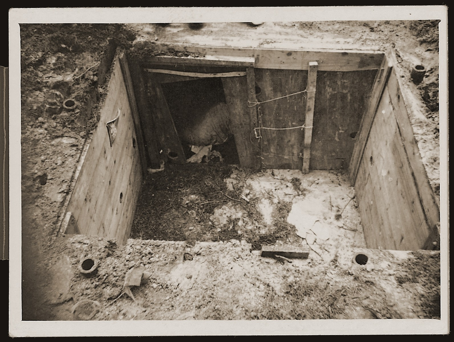 View of the bunker that served as a hiding place for Dutch Jews in the Eibergen region in 1942-1943.  The bunker was discovered by the Germans one day before this photograph was taken.  The bunker was, in actuality, a prefabricated hut that was ordered by two Jewish brothers, Abraham and Herman Maas from Eibergen.  It was delivered in sections to a site in the Hoones Forest outside Eibergen.  The Maas brothers got permission from the manager of the privately-owned forest to build a subterranean hiding place for themselves.  Two sympathetic non-Jews conveyed the materials, dug the hole and assembled the shelter, which had two rooms and a crude stove.  Initially, only the brothers hid there, but as times grew more desperate, 23 Jews were concealed in the bunker.  On March 27, 1943 a Dutch informer led Germans to the site.  All 23 were arrested and sent to Westerbork.  From there they were deported to Sobibor and killed.  After the war the informer was identified as E. Heijink and tried as a collaborator.  The photographer was a Dutchman, who was ordered to take pictures of the bunker the day after the Jews were captured.  He made an extra set of prints, which he kept secretly, and made available to resisters and surviving Jews after the liberation.  The policeman posed inside the bunker in order to better convey its size.
