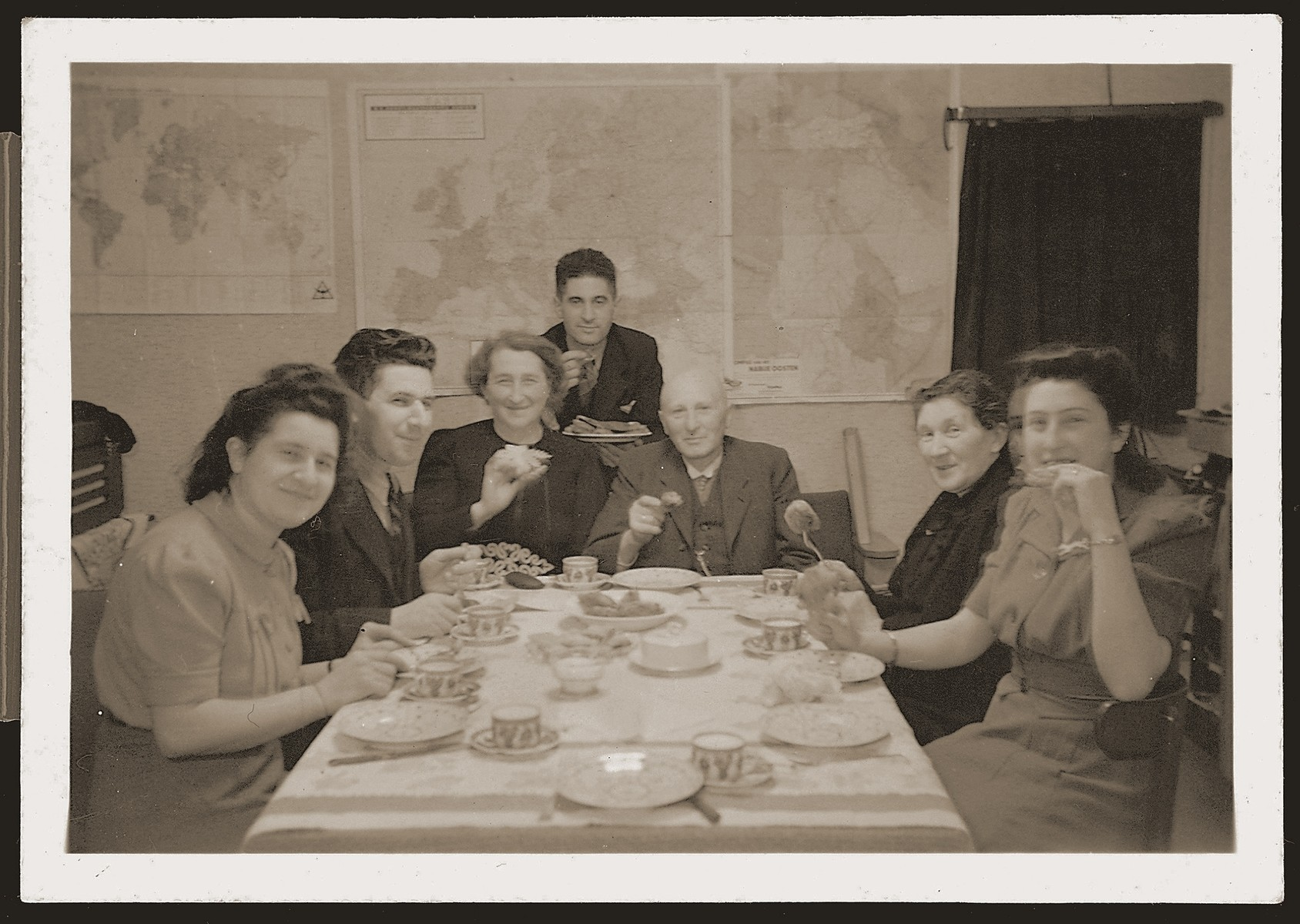 The Meijer family from Borculo is invited to dinner at the Zions in Eibergen.  It is the first meeting of the two families since their children, Bep and Sallie, began to date.  Pictured from right to left are:  Bep Meijer; Bethje Gans Zion; Joseph Meyer; Zadok Zion; Hennie Meyer Meijer; Julius Zion; and Wilhelmina Zion.  Posted on the wall behind them are maps of Europe with pins indicating the progress of the war.