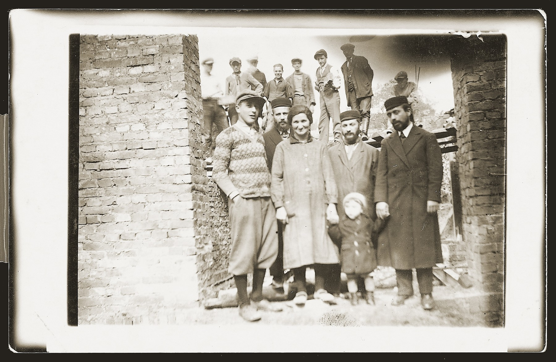 Members of the Gelbard family stand in the brick frame of a half-constructed building.  Among those pictured is Ita Gelbard.