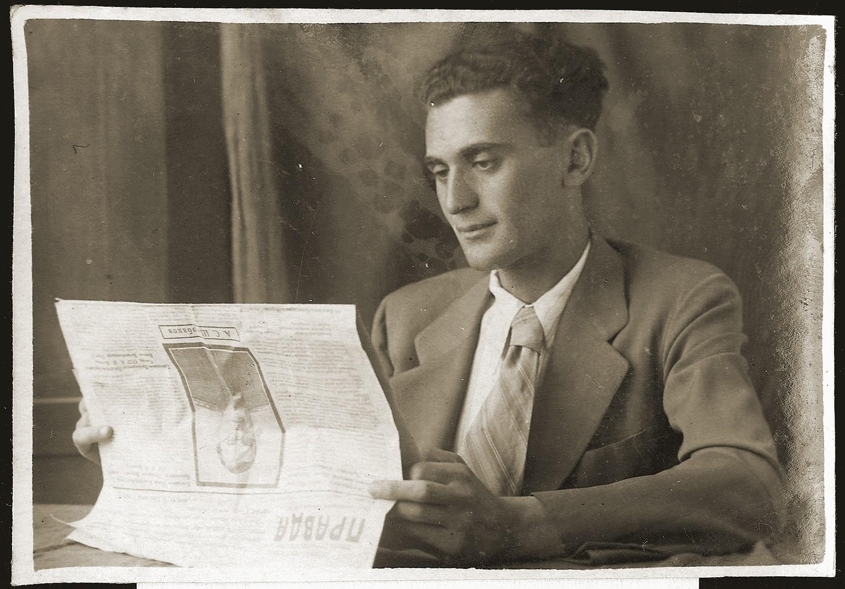Salek Liwer reading the Russian newspaper, Pravda, in his room in Bukhara.
