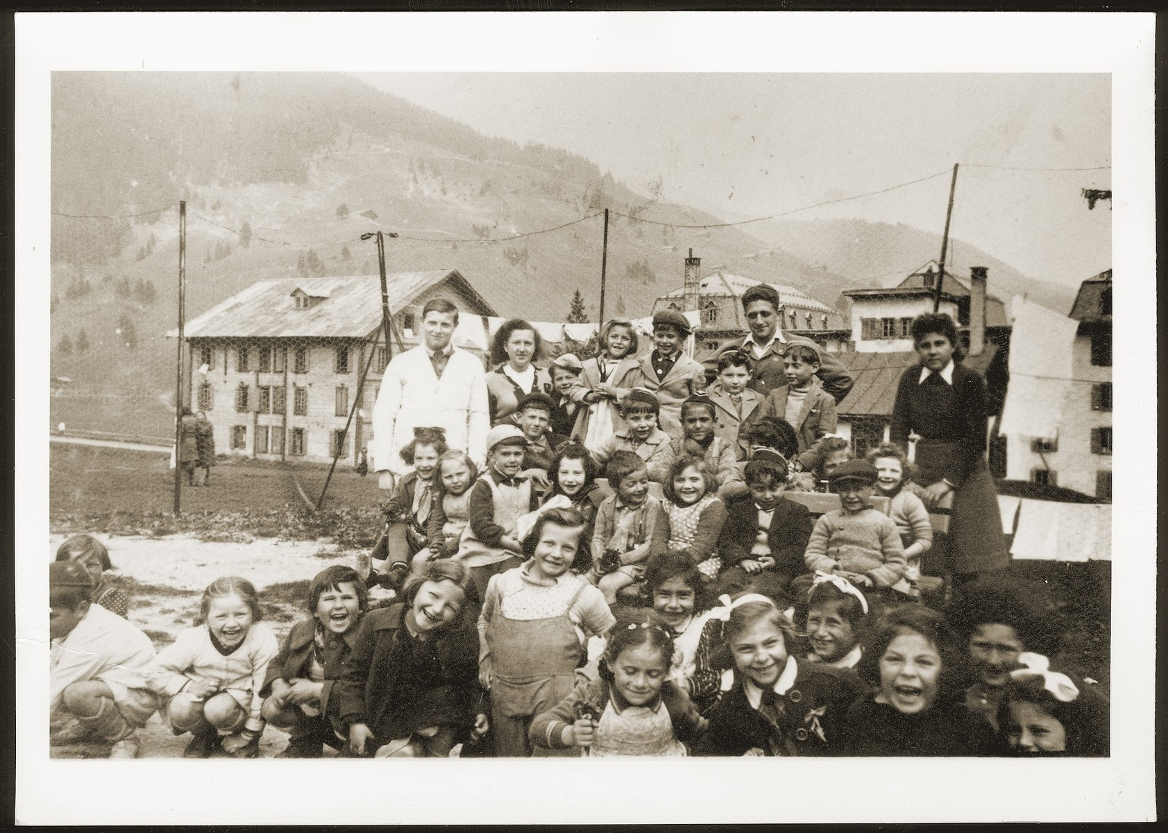 Children in the in the Morgins refugee camp school pose with their teacher by a fence.  Frieda Johles is standing in the front center.