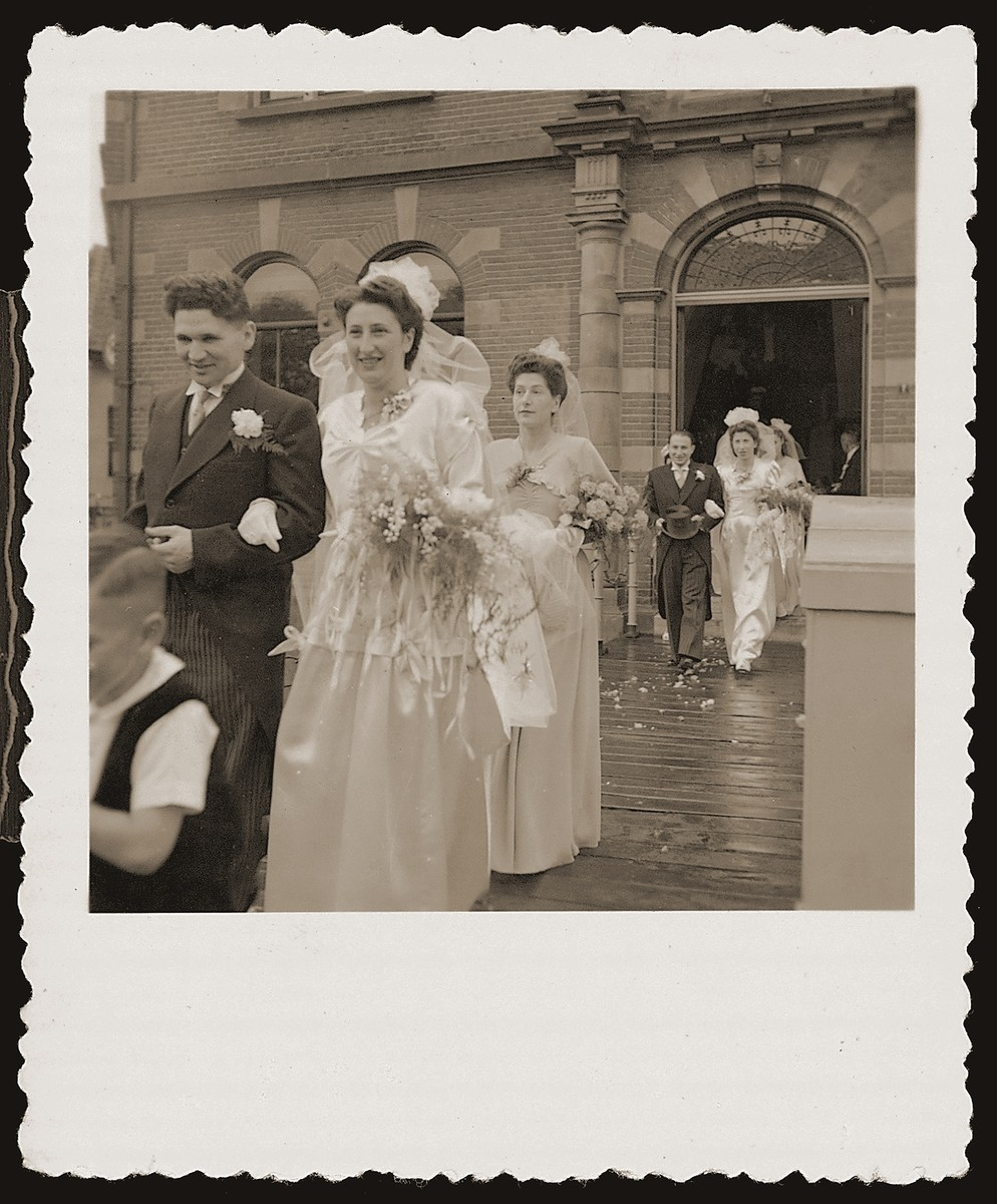 Two Jewish couples and their attendants file out of the city hall in Boekelo after a joint civil marriage ceremony.  They are now on their way to a local hotel, where the religious ceremony will take place.   Pictured in front are Bep Meijer and Sallie Zion and behind, Mathilde Hartog and Richard Meijer.  Neither couple could afford the cost of a private ceremony.