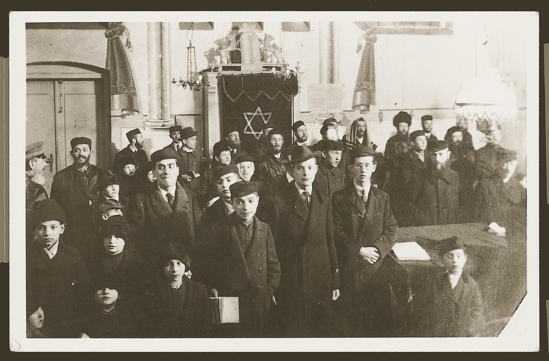 Religious men and boys pose in the Czeladz synagogue.  This picture was taken during WW I by a German soldier.  Standing close to the wall on the right side with the fur hat , is the town's rabbi  Rabbi Lippman Hersh (Eliezer Zwi) Lewenthal.
