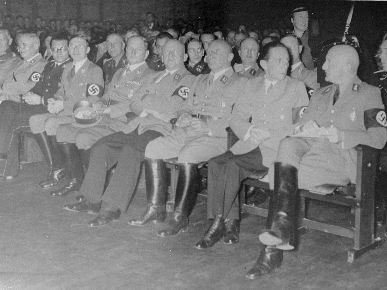 "Julius Streicher, Joseph Goebbels and other Nazi officials attend the opening ceremony for ""The Eternal Jew"" in Munich.  The individuals in the front row (left to right) have been identified as General Werner von Blomberg (partial view), Ludwig Siebert, Phillip Bouhler, Karl Fiehler, Franz Xaver Ritter von Epp, Adolf Wagner, Julius Streicher, Josef Goebbels, and Otto Nippold. Pictured in the second row, between Goebbels and Streicher is  Deputy Gauleiter Georg Tesche."