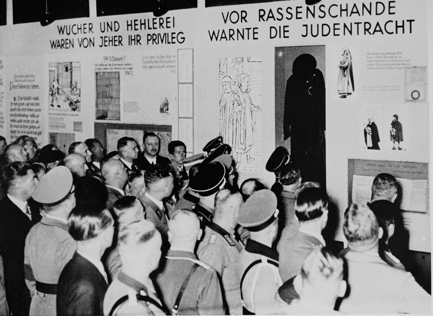 """Nazi officials in attendance at the opening of """"The Eternal Jew"""" exhibition in Munich, view a segment entitled, """"Jewish dress was a warning against racial defilement.""""  To the left is a segment entitled, """"Usury and the fencing of goods were always their privilege."""""""