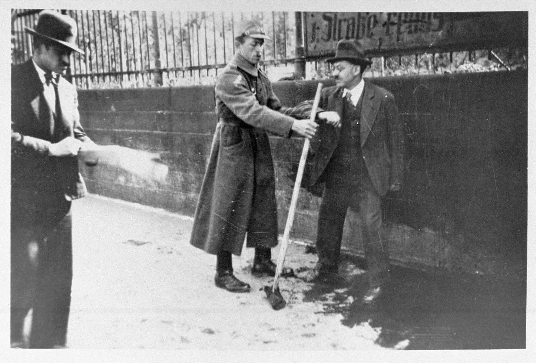 A Nazi forces a German Jew to take a broom and sweep the pavement.  During the sporadic wave of attacks on the Jewish-owned shops in Germany during 1938-1939, many Jews were accosted in the streets and subjected to public humiliation through forced labor.  One of the Nazi's favorite acts of forced labor was to compel Jews and other dissidents to sweep city streets and clean walls.