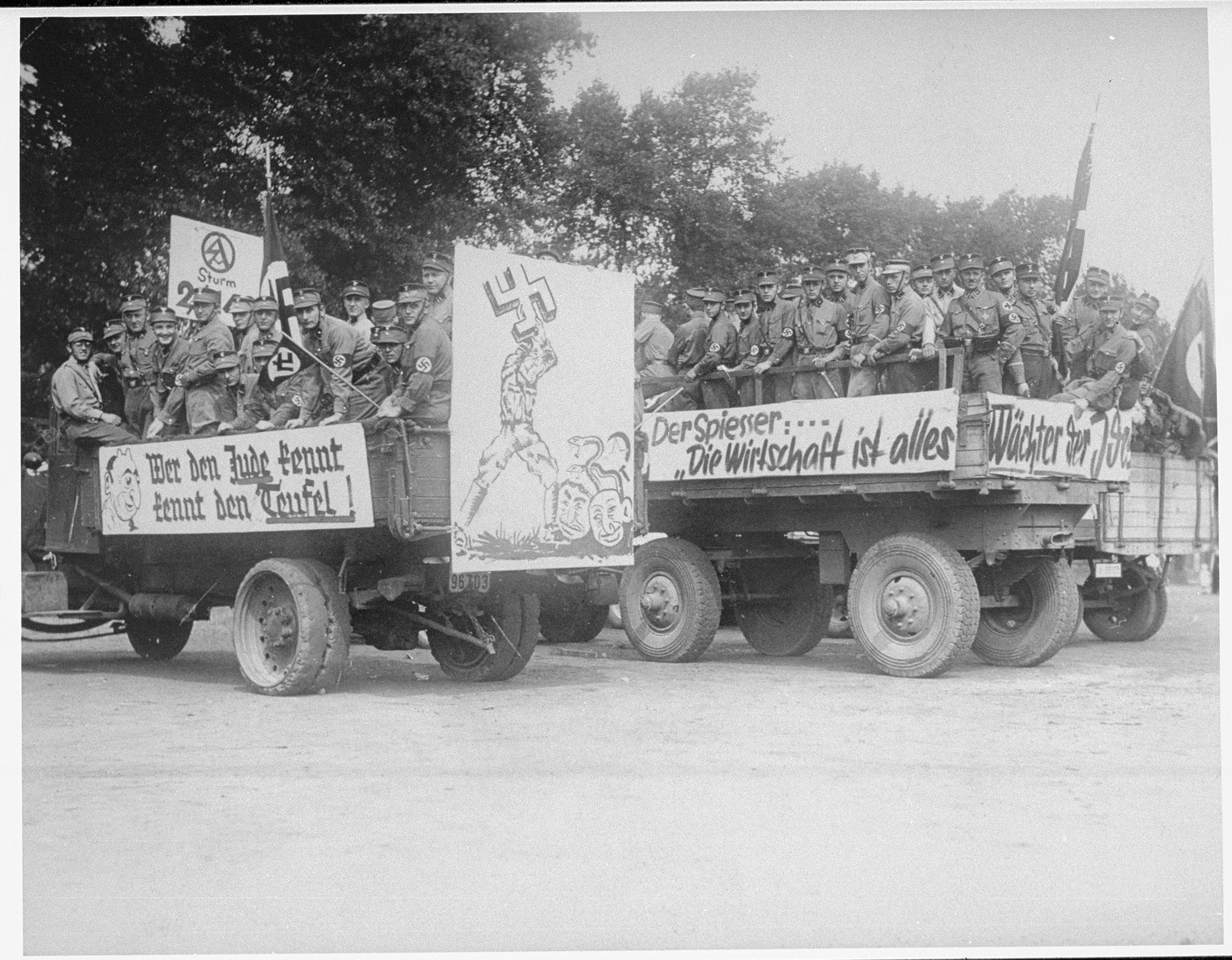 "Members of the SA drive through the streets of Recklingshausen, Germany on propaganda trucks bedecked with anti-Jewish banners.  The banners read: "" He who knows the Jew knows the Devil,""  ""The Bourgeois: 'the economy is everything.""  The poster depicts a man using a swastika to crush Jews with snakes coming out of their heads.  On the back is the official stamp of the SA and a handwritten note, ""At the beginning of the Propaganda parade on August 18, 1935."""