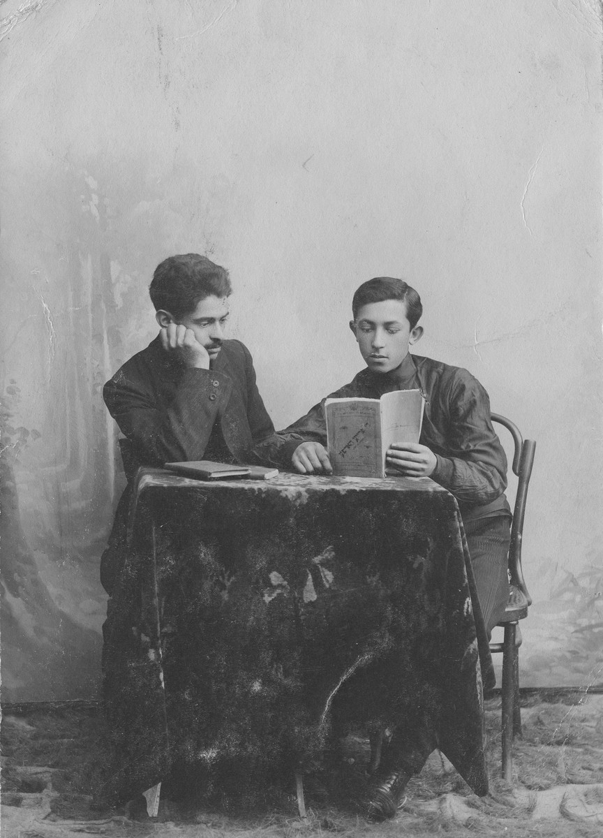 Studio portrait of two young Jewish men posing with a book taken in Kaunas in the early 1900s.