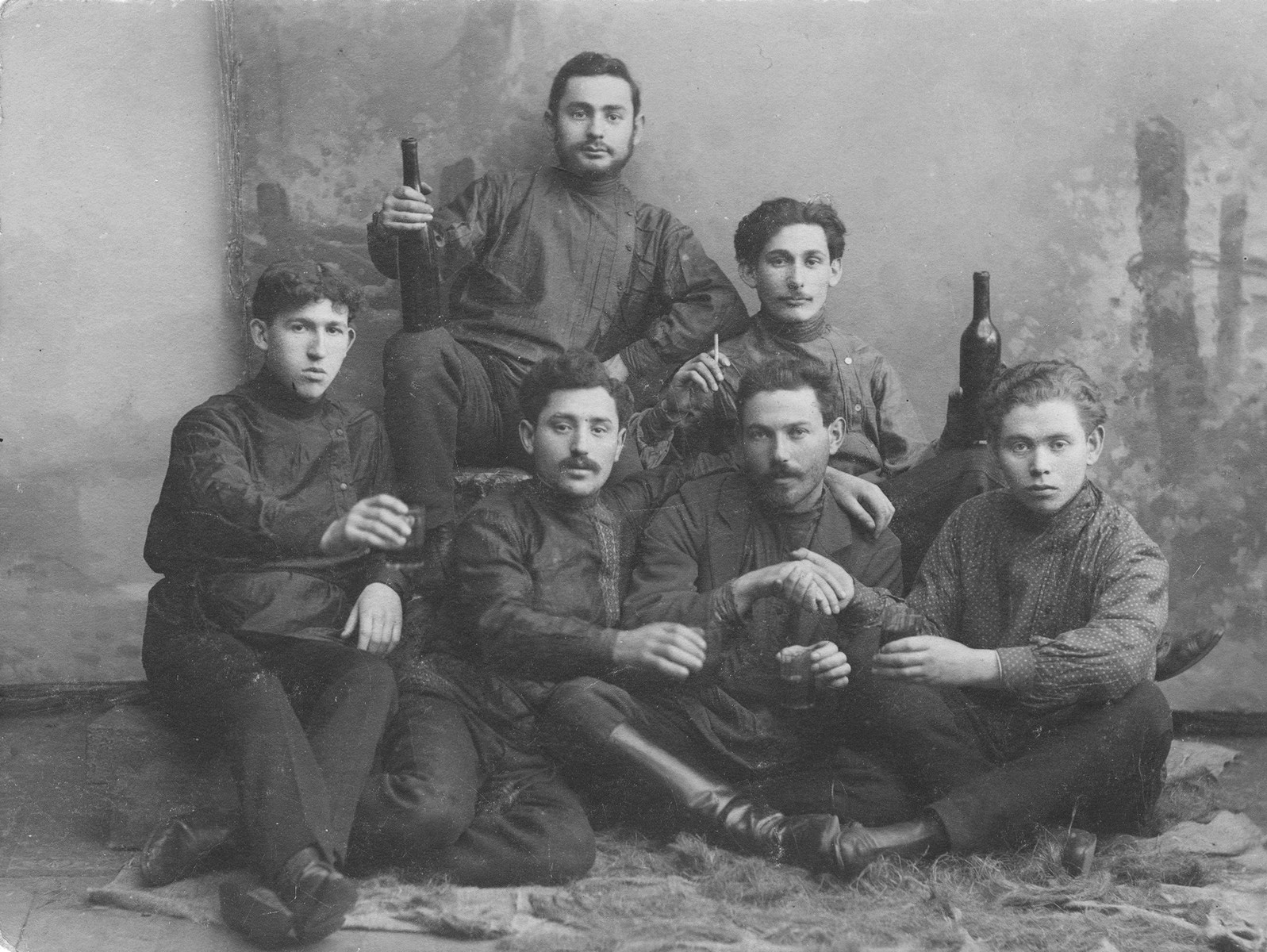 Studio portrait of a group of young Jewish men posing with wine bottles taken in Kaunas in the early 1900s.