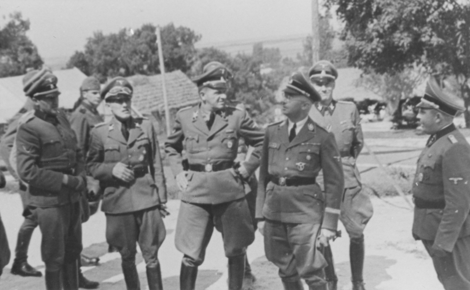Reichsfuehrer SS Heinrich Himmler (center, right) on an official tour of a Jewish labor camp along the main supply route in Galicia.  Also pictured is camp Commandant Friedrich Warzok (far right), SS Gruppenfuehrer Hanns Johst (center), and SS Gruppenfuehrer Fritz Katzmann (second from the left with his hand on his belt).