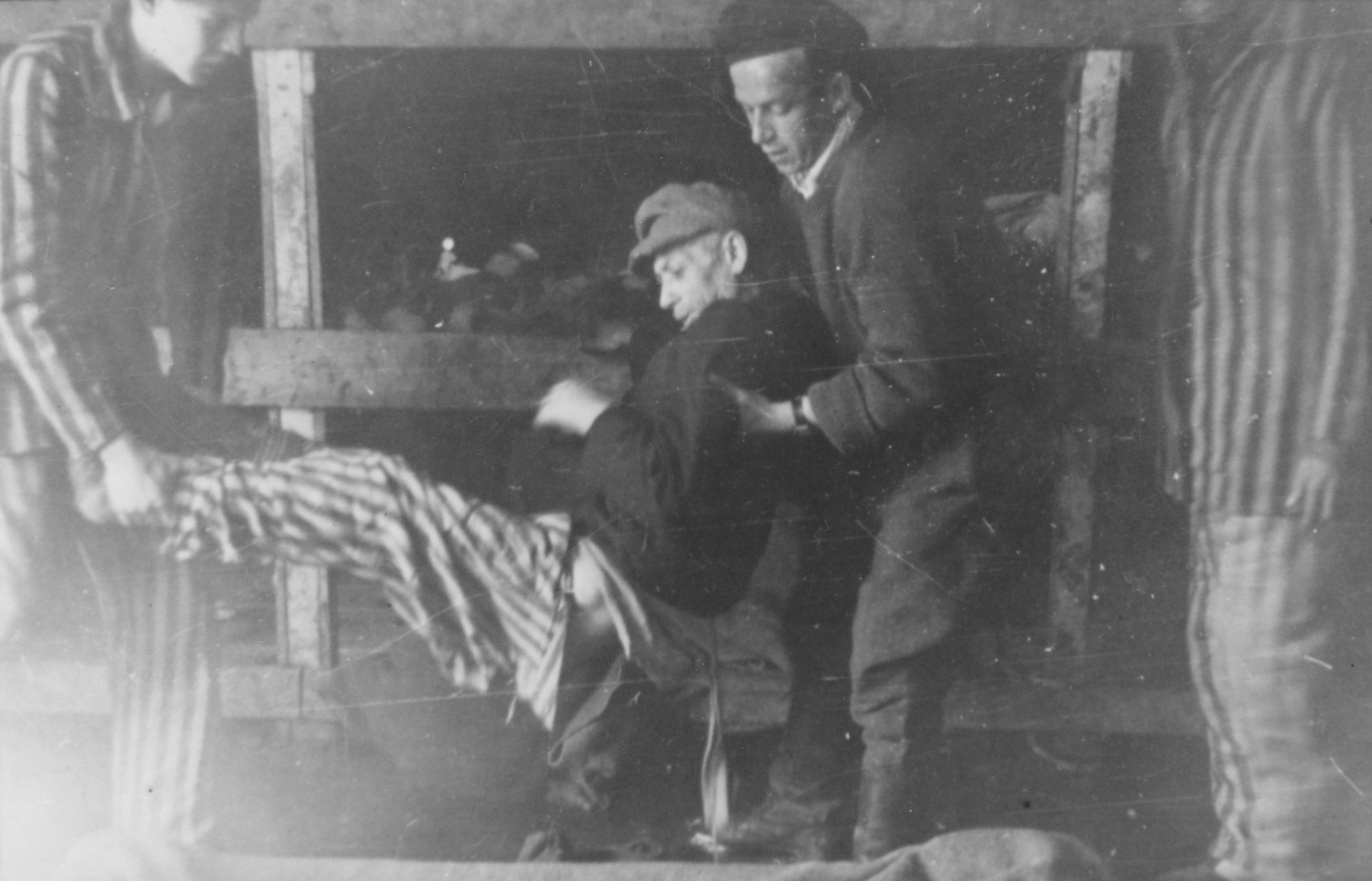 Two survivors lift a weaker comrade from a bunk to a stretcher in a barracks in the newly liberated Buchenwald concentration camp.