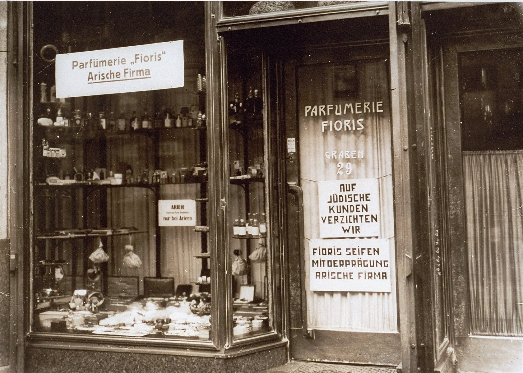 """View of a perfume shop in Vienna with posted signs certifying that the enterprise is an Aryan firm.    The German signs read, """"Floris Perfume Shop, Aryan Firm;"""" """"We refuse to serve Jewish customers;"""" and """"Fioris soaps, with the stamp of an Aryan firm."""""""