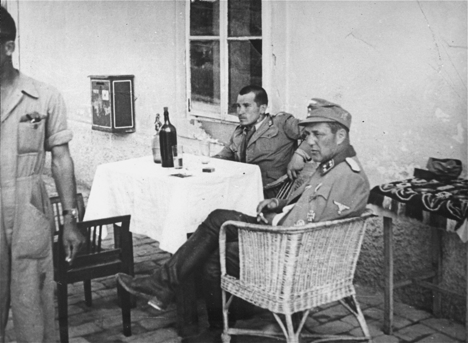 Vjekoslav Luburic sits at a table with a German officer in the Stara Gradiska concentration camp.