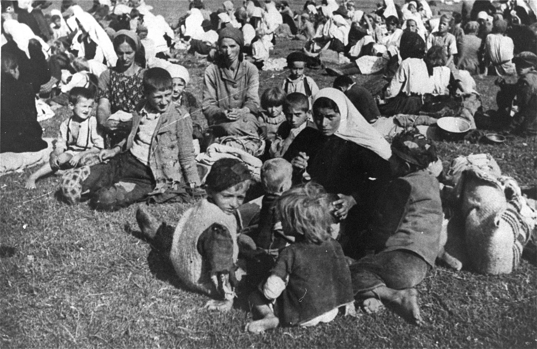 Serbian women and children from the Kozara region who have been deported from their homes, sit outside at the Daruvar concentration camp.