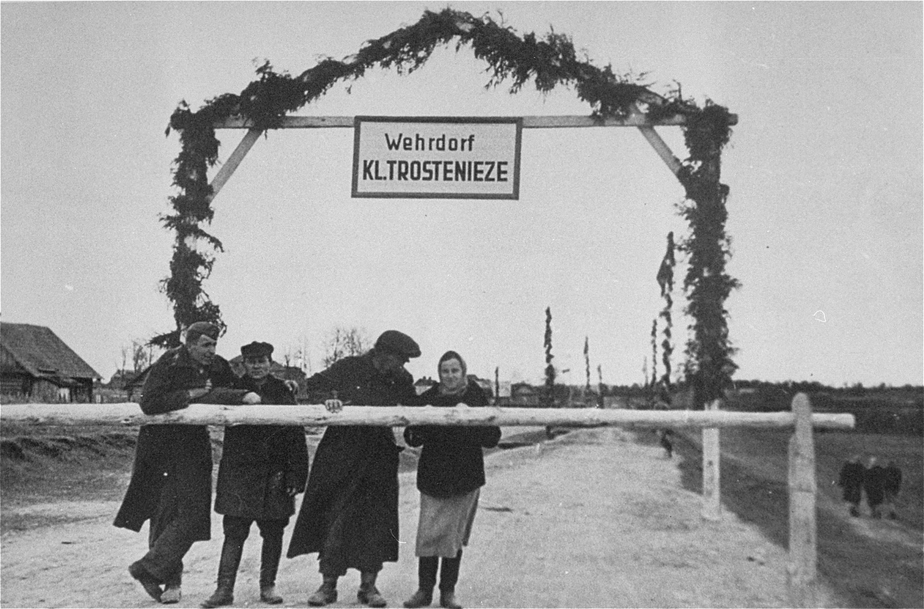 Three men and a woman stand behind the guard rail at the entrance to the Maly Trostinets concentration camp.