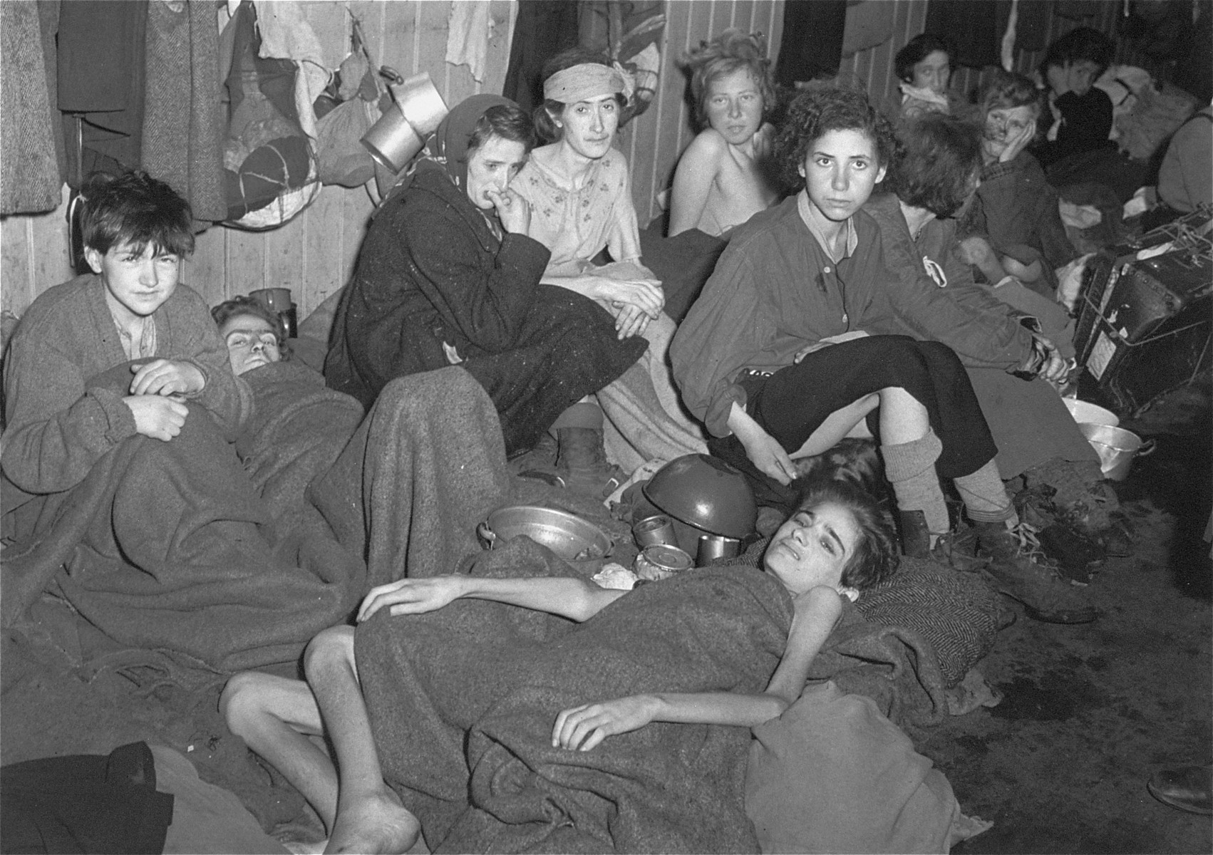 """Women and children, many of whom are suffering from typhus, typhoid, and dysentary, in a barracks at Bergen-Belsen after liberation.  The original caption reads: """"Inside the hospital, so termed.  Most of the inmates are dying."""""""