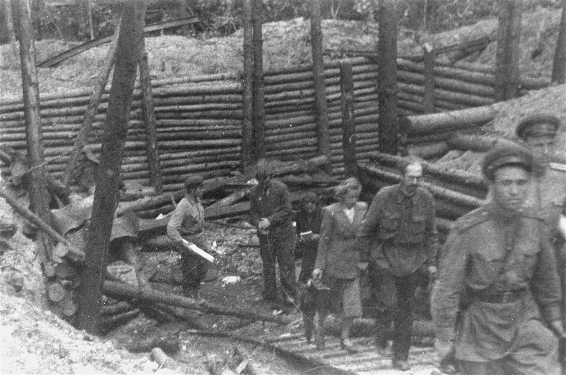 Soviet soldiers and investigators view the site where the corpses of Jewish prisoners were burned in the Maly Trostinets concentration camp.