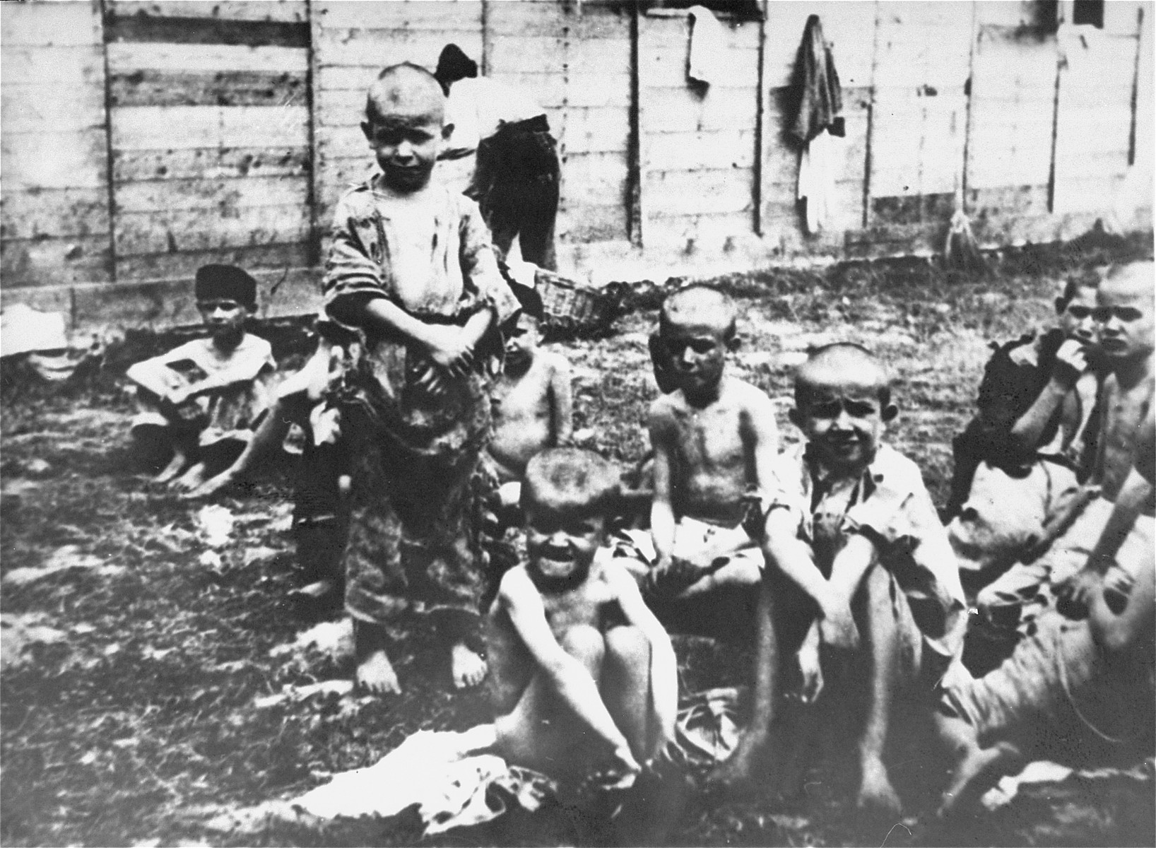 Emaciated Serbian children from the Kozara region sit outside in the Stara Gradiska concentration camp.