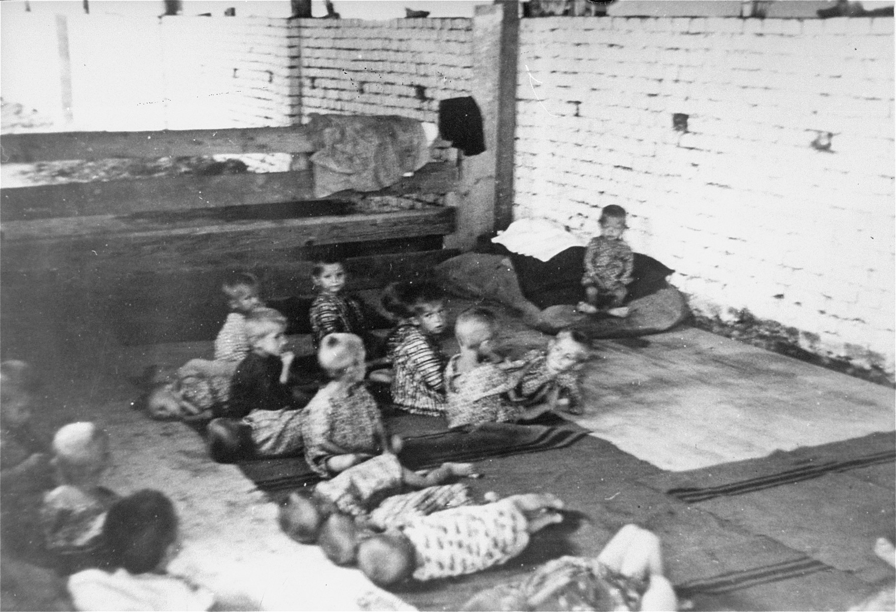 Young children resting on the floor in a barracks at the Sisak concentration camp for children.