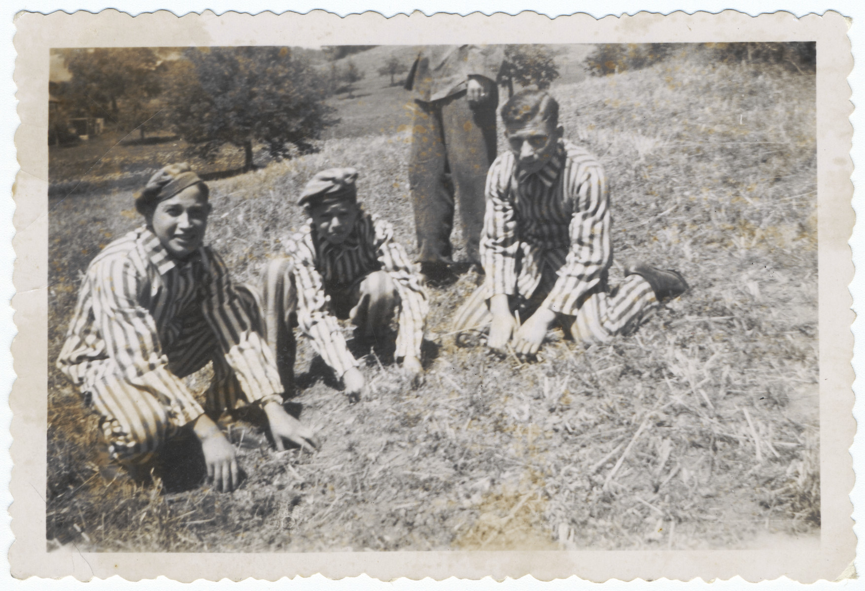 Three Buchenwald survivors pose on the grass in their uniforms after liberation.