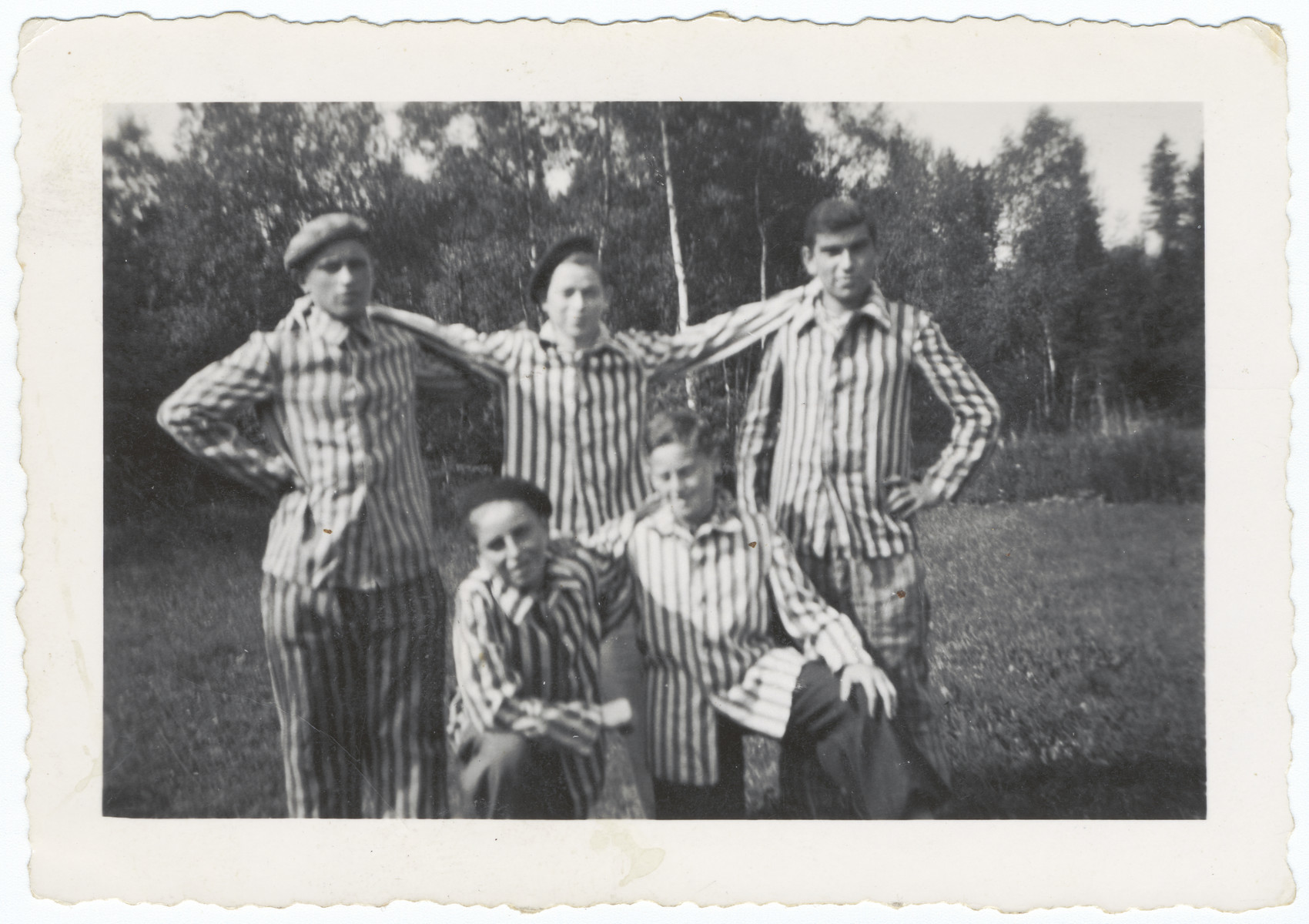 Portrait of five young survivors of the Buchenwald concentration camp in their uniforms.