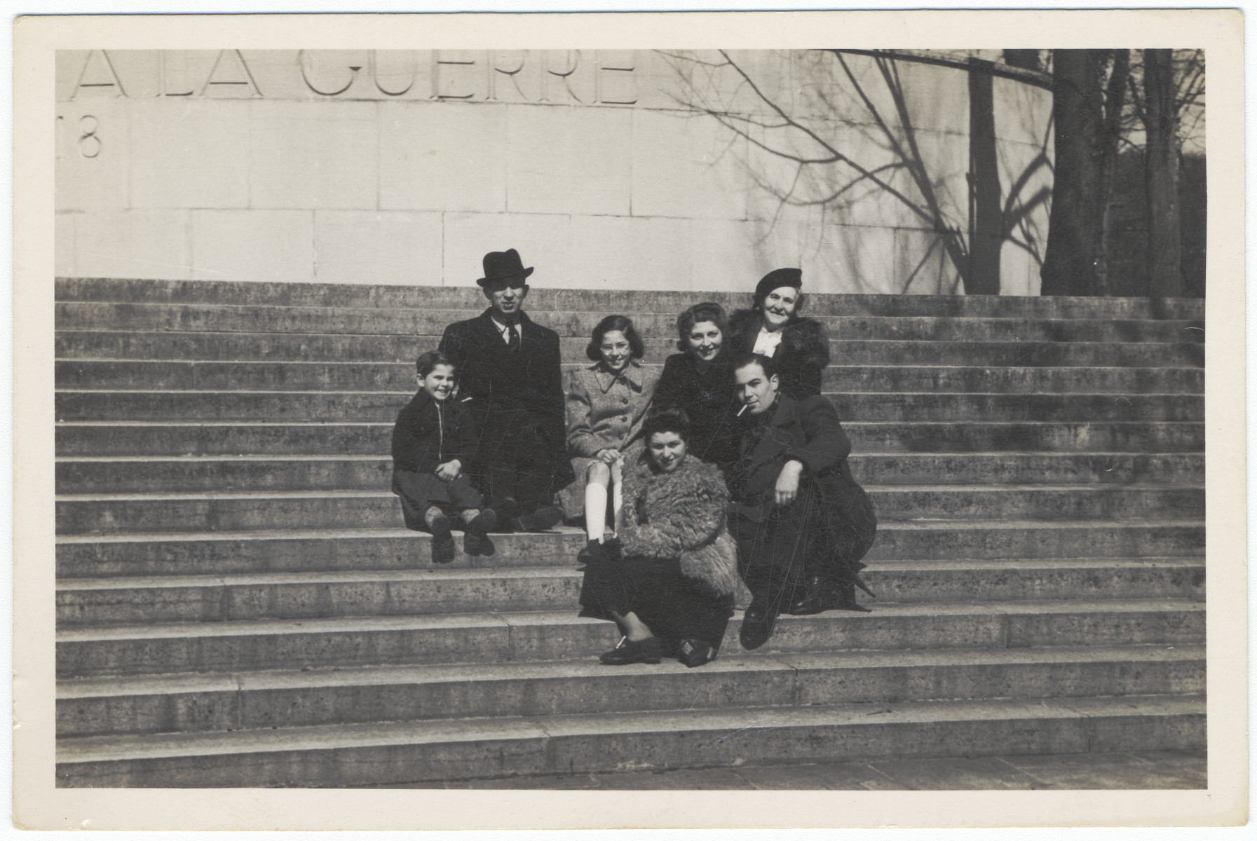 A Jewish family and their friends pose on the steps of a war memorial in Lyon where they are living semi-clandestinely under their own names.  Pictured in the back from left to right are Josey, Alexander, Renee, Luba and Yetta Fainas.  In front are two friends.