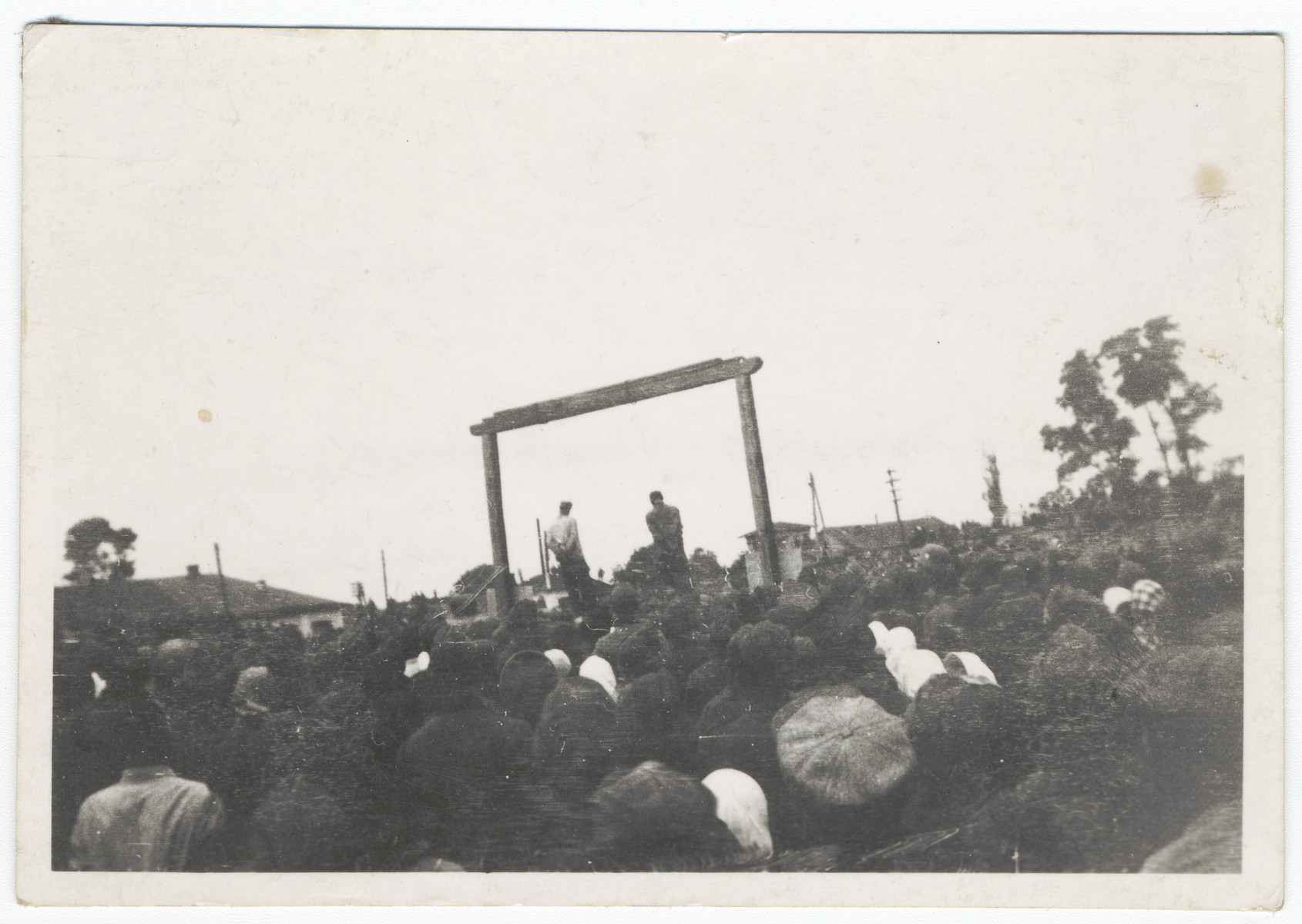 """Spectators witness the public execution of Mosche Kogan and Wolf Kieper.  The original caption reads """"Jewish judges and executioners now being executed""""."""