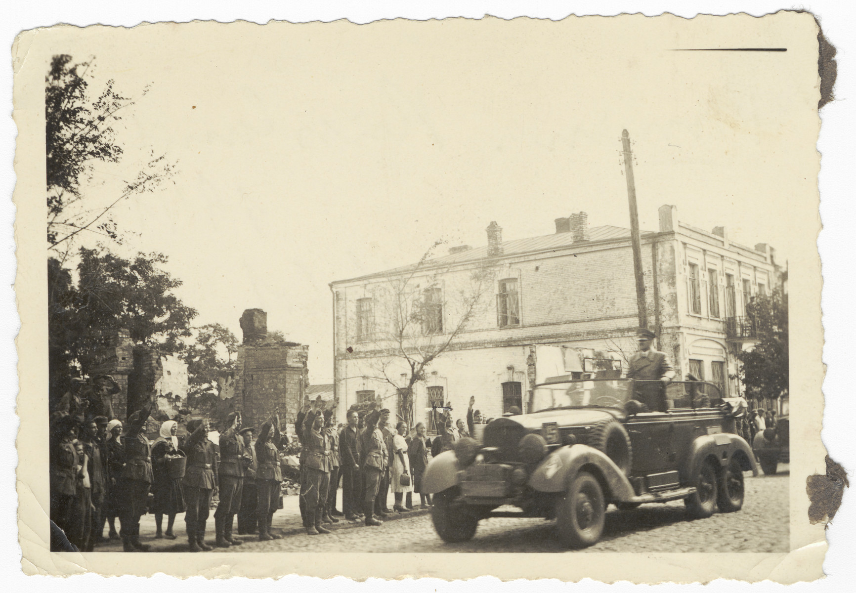 Czech civilians stand and greet Hitler as his motocade rolls by.