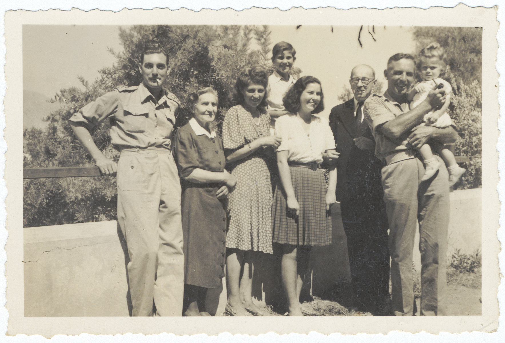 A Jewish family poses with American soldiers and the mayor of the town after liberation.  From left to right are an American soldier, Yetta, Luba, Josy and Renee Fainas, the mayor of the town who was also in the resistance and another American soldier.