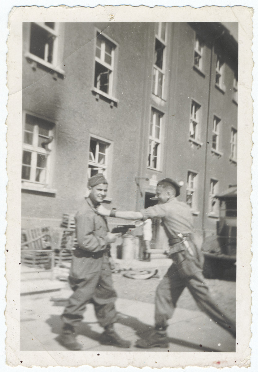 Two young survivors play fight outside a building in the liberated Buchenwald concentration camp.