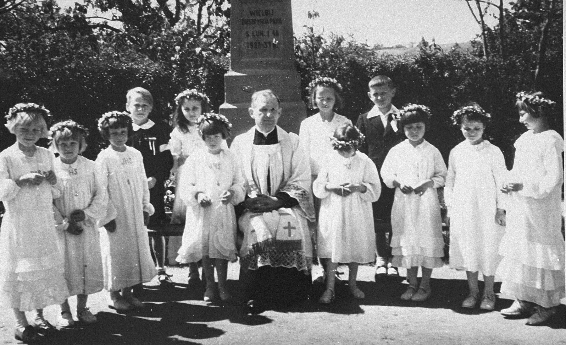 A Jewish child in hiding stands among a group of Polish children dressed up for their First Communion.  Pictured fifth from the left is Eve Nisencwajg.