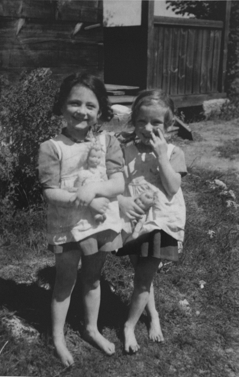 Twin sisters Sylvia and Anna Morgenstern pose with their dolls while living in hiding in occupied Poland.