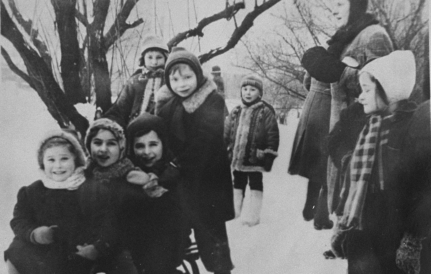 A little Jewish girl living in hiding in Warsaw, goes sledding with a group of Polish children.  Pictured at the far left is Rita Berkowicz, the donor's daughter.