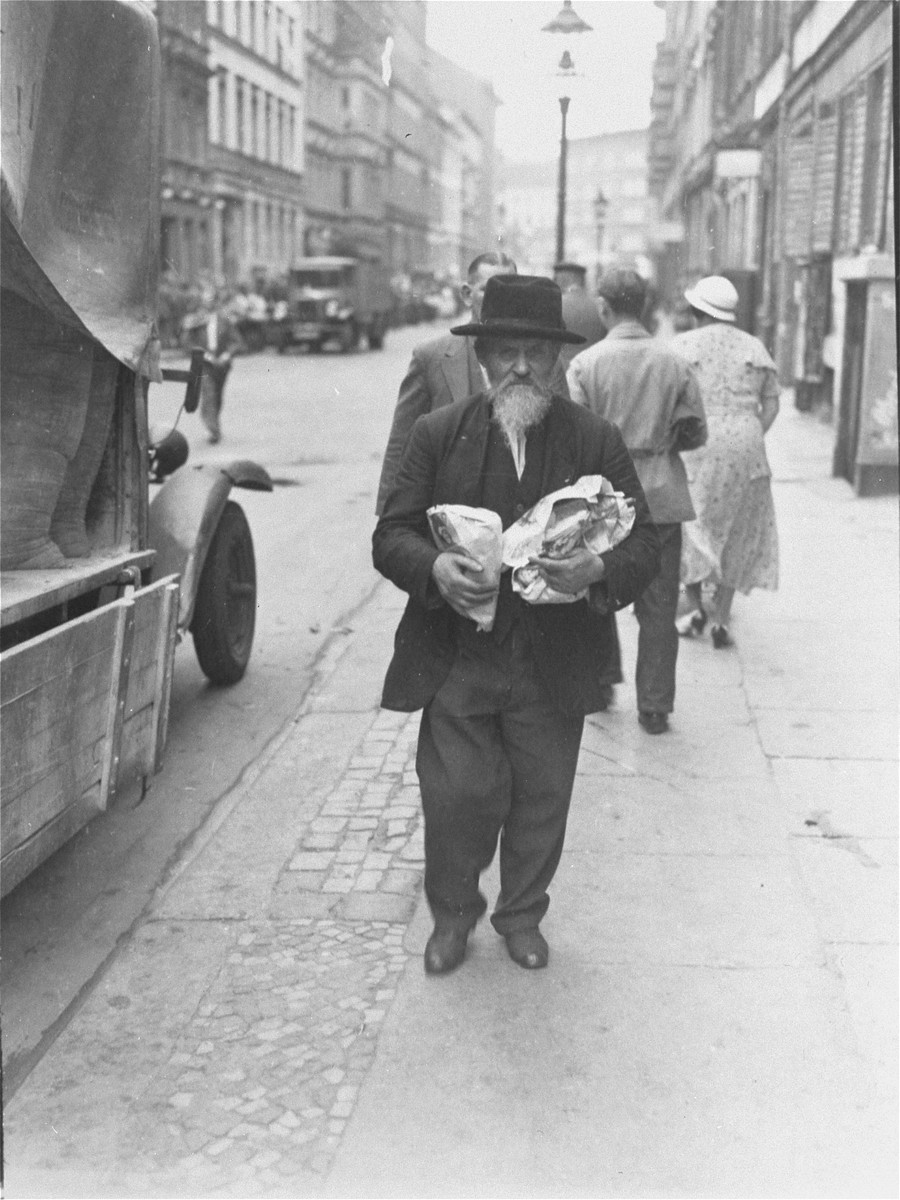 A Jewish man carrying two bags walks down the main commerical street of the Berlin Jewish quarter.