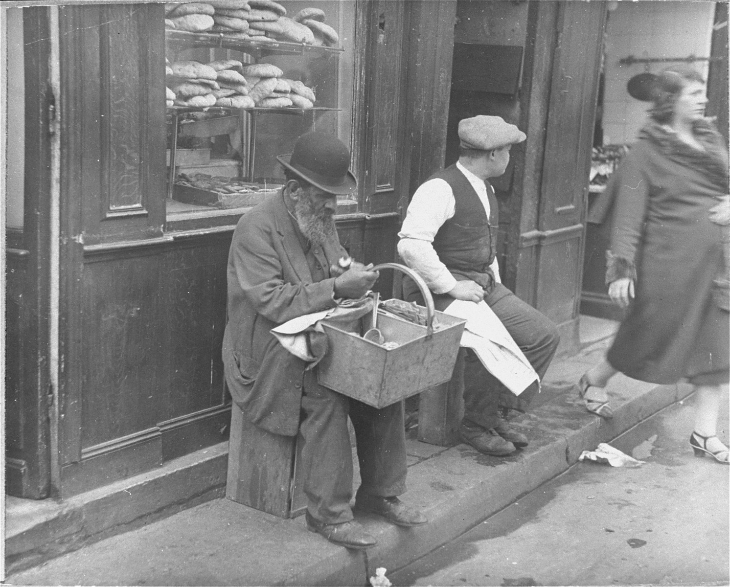 A Jew sells peanuts in front of a bakery in the Jewish quarter of Paris.