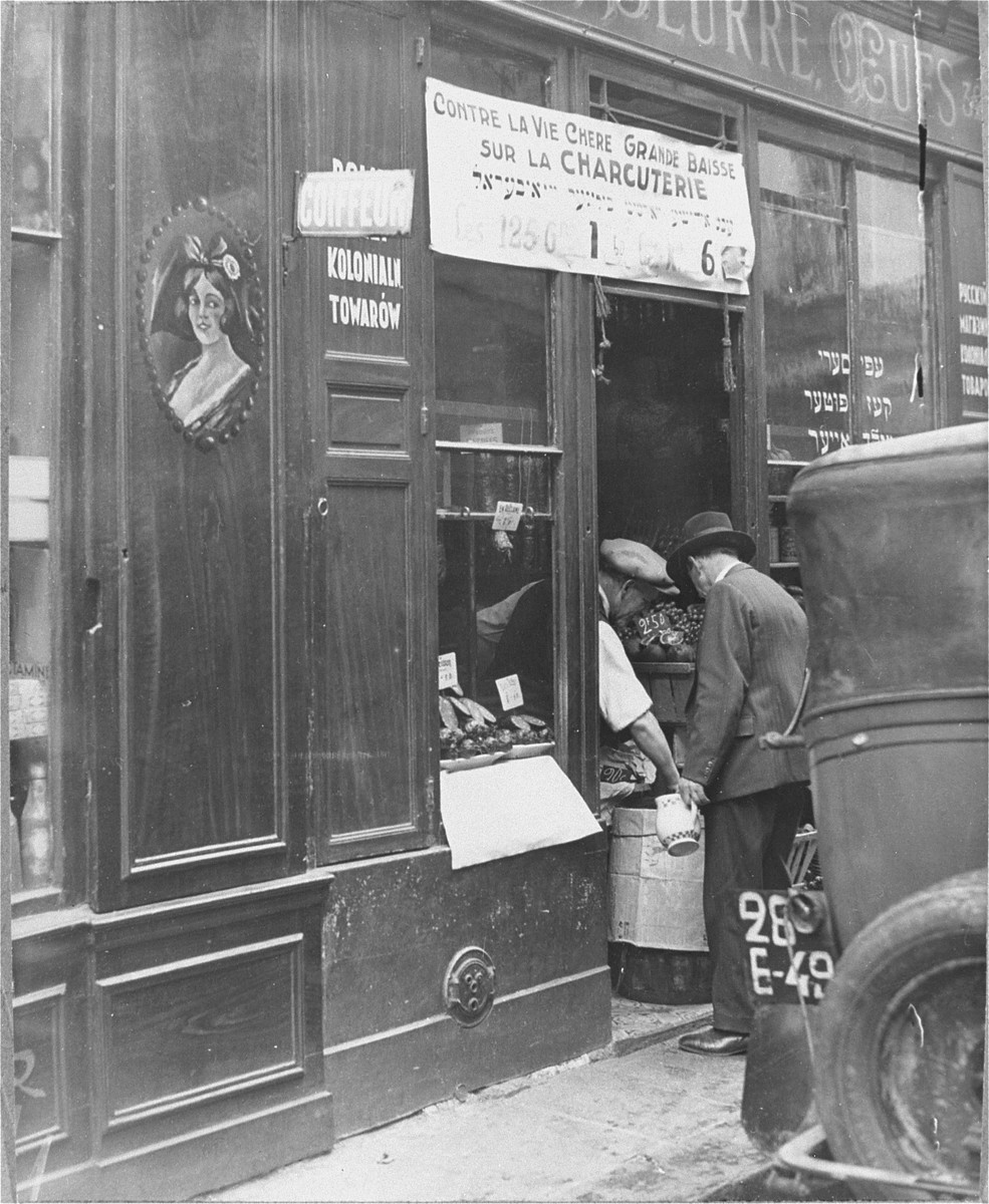 A Jewish shopkeeper helps a customer in the doorway of his grocery store in the Jewish quarter in Paris.