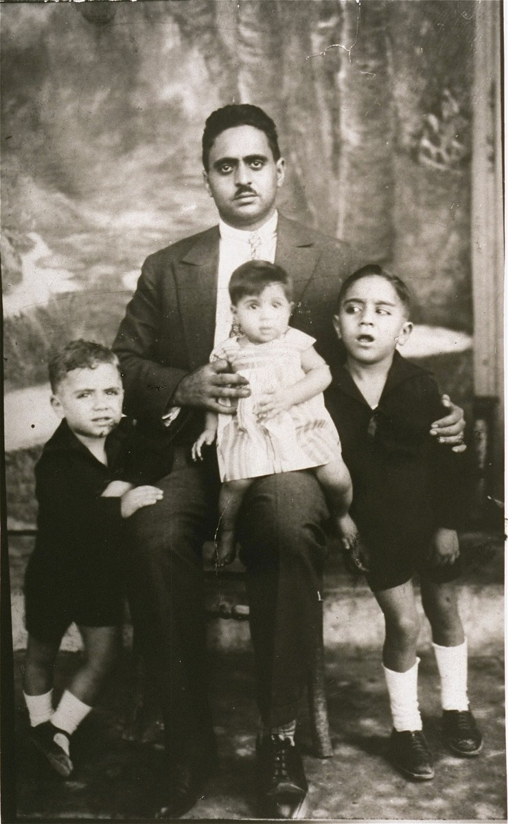 Portrait of the Mordo family in Corfu.  Pictured are Jacob Mordo and his three children: Perla (the infant on her father's knee), Moses (left) and another son (right).