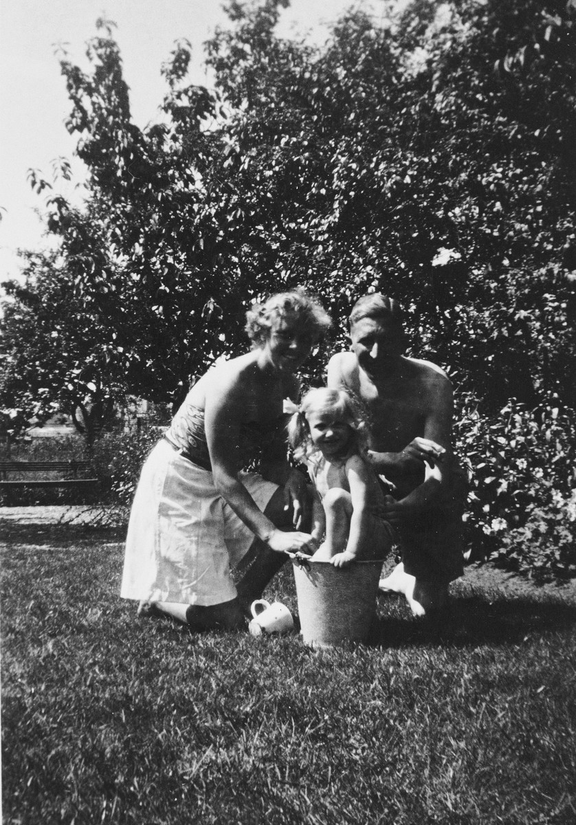 Siny Natkiel plays with a bucket in a garden along with her rescuers, Dr. Herman and Nel Mayer.