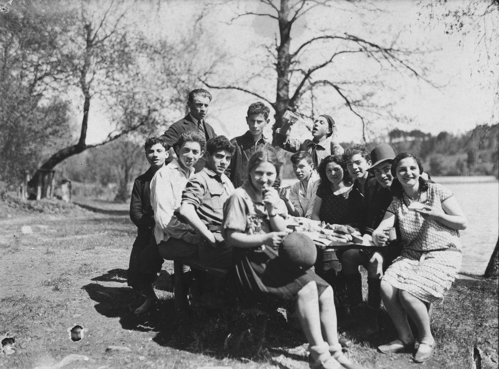 Members of the Morgenstern Jewish sports organization pose around a picnic table while on an outing to the lake.  Among those pictured are Shimke Isaac, Reike Epstein and Avremke.