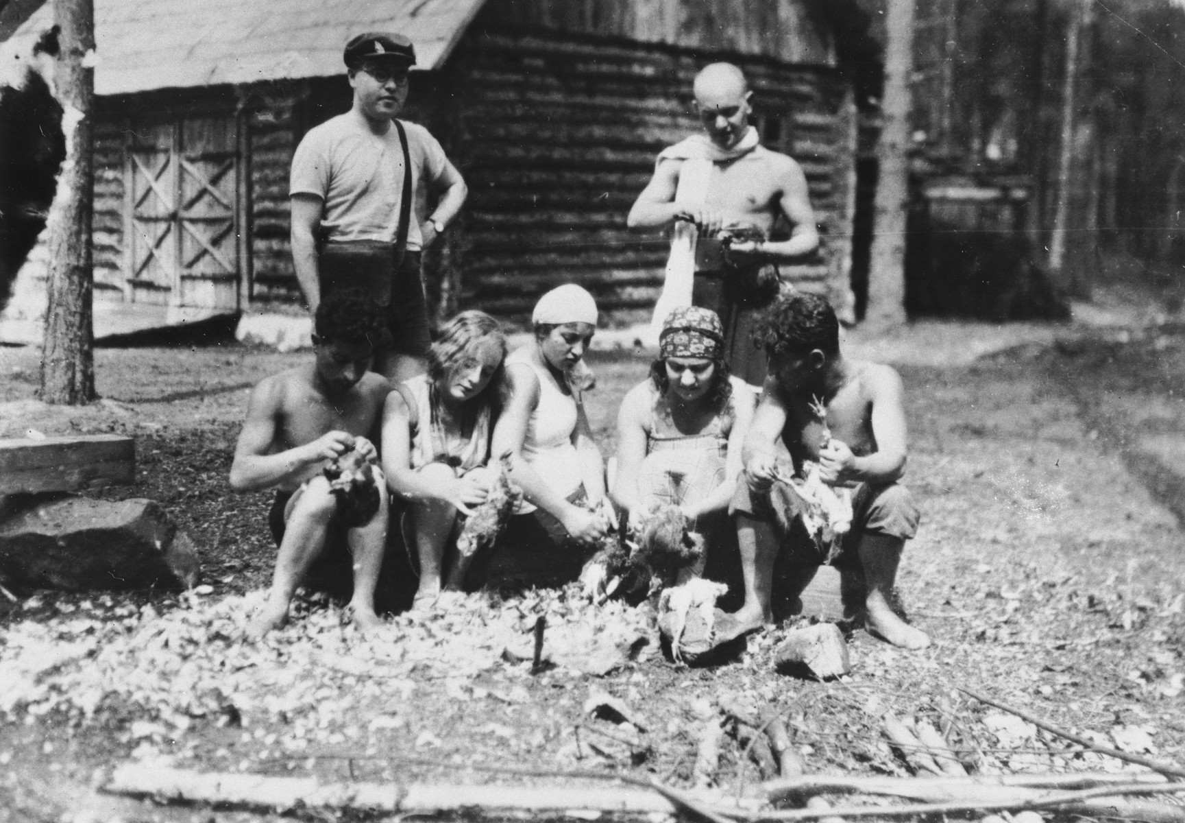 A group of young people pluck chickens outside a log cabin in Narocz, Poland.