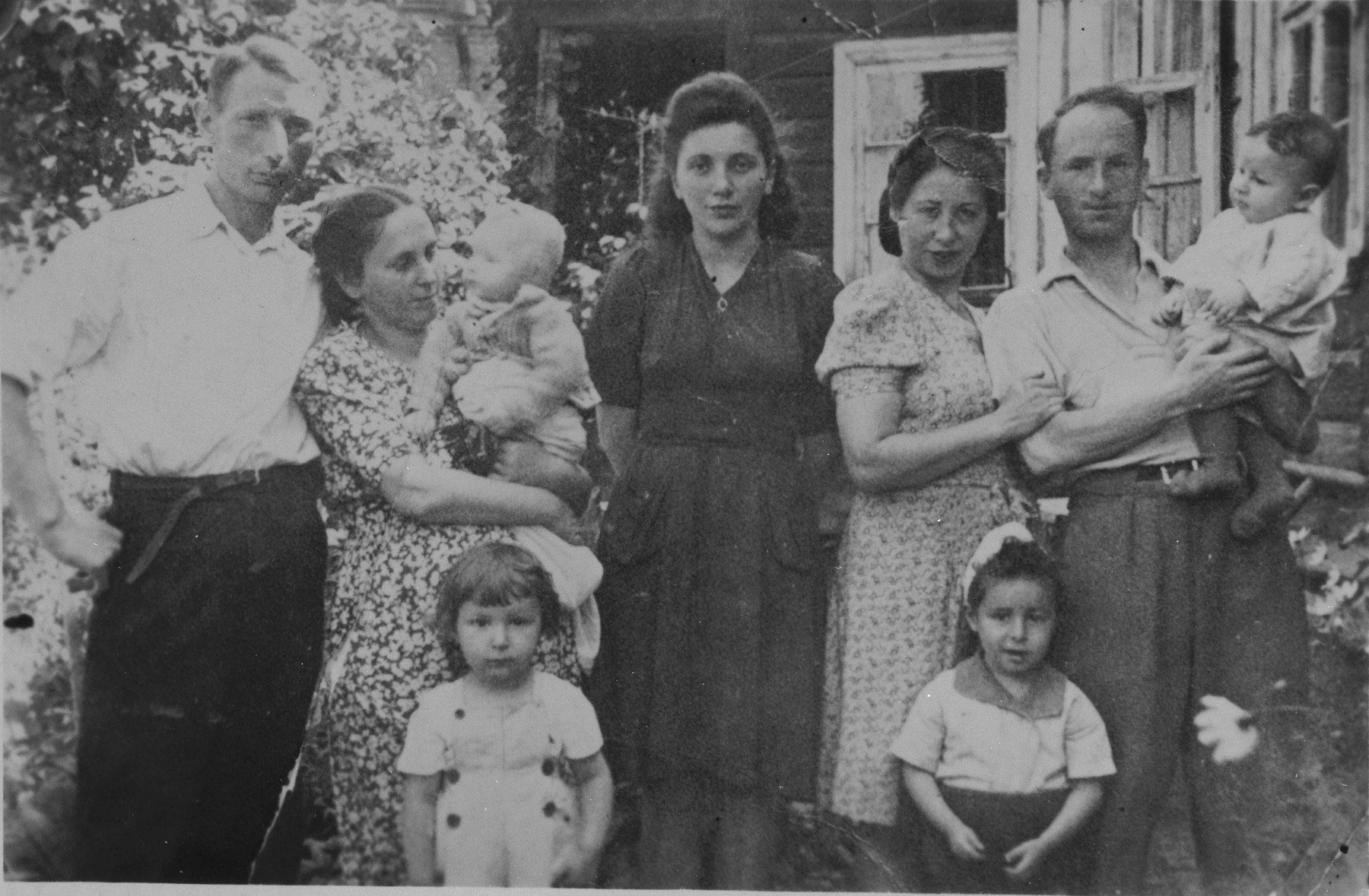 Jewish DP couples pose with their young children outside a home in Minsk.  Pictured are Israel and Julia Matz with their sons Boris and Shaul (at the right), and Lowa and Chaja Lurie with their two children (at the left).