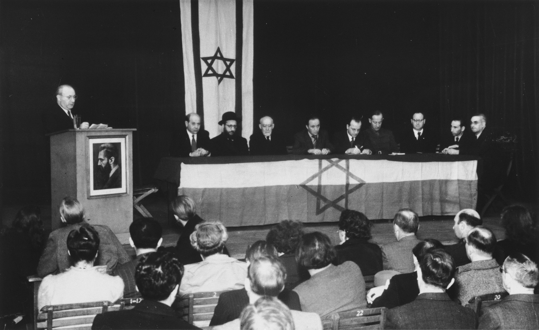 An unidentified Jewish leader delivers a speech at a Zionist meeting in Hannover.  Among those pictured is Rabbi Leo Baeck (seated third from the left).